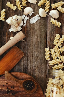 Wooden equipment on kitchen counter with spices and pasta