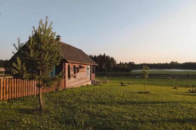 Деревянный европейский дом в живописной сельской местности на закате летом