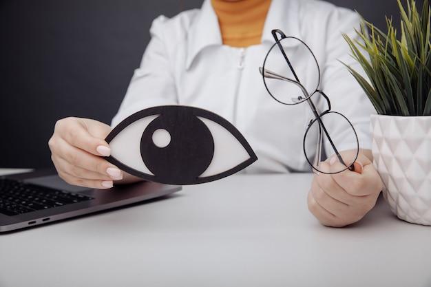医師の手のクローズアップで木製の目とメガネ