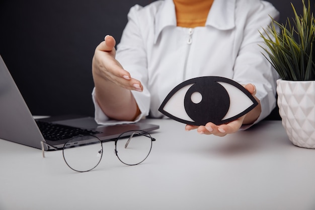 Wooden eye in doctors hand early diagnosis and care concept