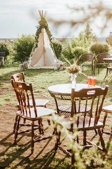 Wooden fabric wigwam decorated with green eucalyptus branches in the backyard, event or wedding in boho style
