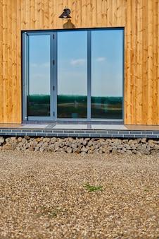 Деревянный фасад деревянного дома. желтая деревянная опалубка. панорамные окна. прекрасный вид отражения в окне голубого неба.
