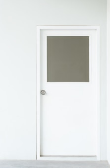 Wooden factory office door with square window on white wall