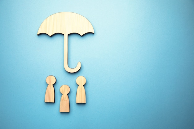 Деревянный знак семьи и зонтик на синей поверхности