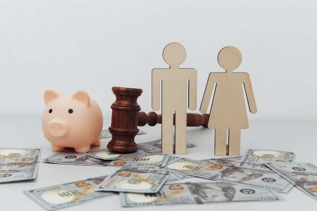 Wooden family figures, gavel and pink piggy bank