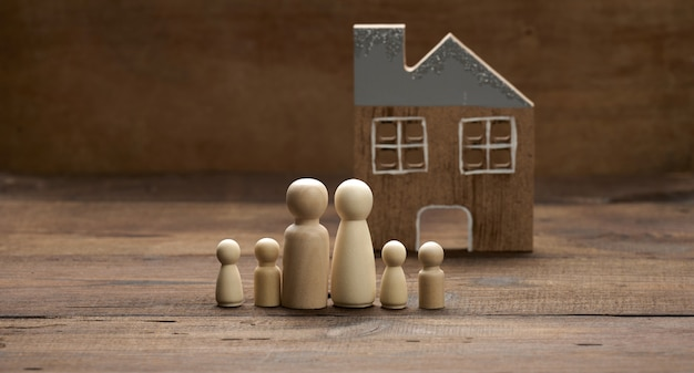 Wooden family figurines, model house on a brown background. real estate purchase, rental concept. moving to new apartments