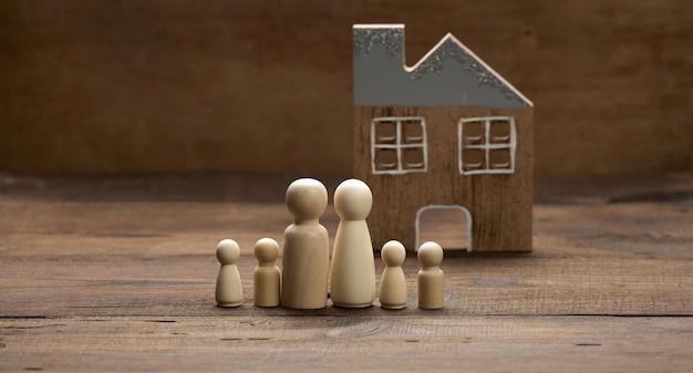 나무 가족 인형, 갈색 배경에 모델 하우스. 부동산 구매, 임대 개념입니다. 새 아파트로 이사