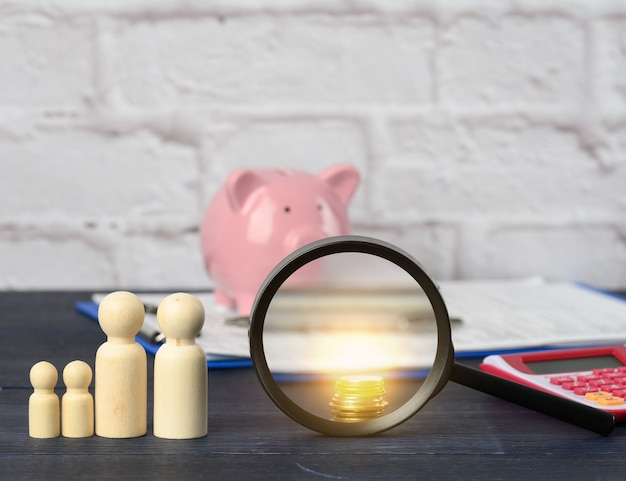 Wooden family figurines and  pink ceramic piggy bank on blue background. concept of accumulating cash for buying a house and a car, money in the bank at interest, payment of subsidies