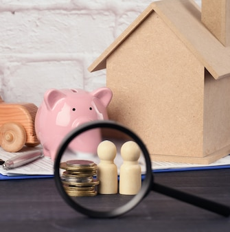 Wooden family figurines and  pink ceramic piggy bank on blue surface. concept of accumulating cash for buying a house and a car, money in the bank at interest, payment of subsidies
