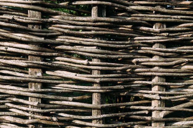 柔軟な茶色の枝から組み立てられた木製のフェンス