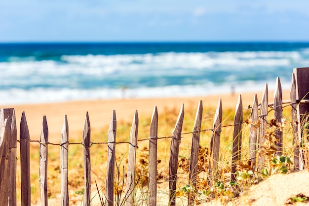 Wooden fence on an atlantic beach in france, the gironde department. shot with a selective focus