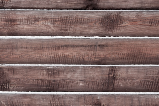 Wooden fence background with snow lying on the boards