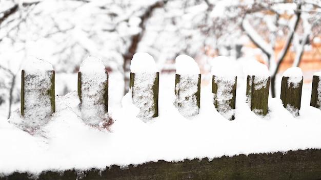 눈이 많이 내리는 눈보라에 하얀 눈으로 덮인 나무 울타리 문, 배경의 덤불. 배경 이미지로 나무 울타리에 눈.