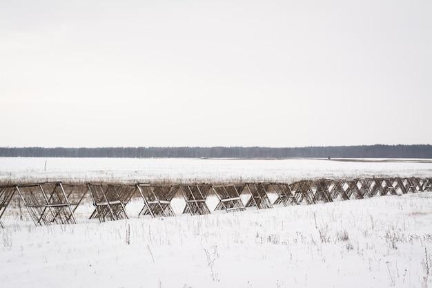 Деревянный забор в поле для защиты дороги от метели зимой
