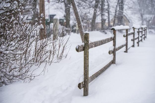 冬の国の背景に雪の中の木製のフェンス。