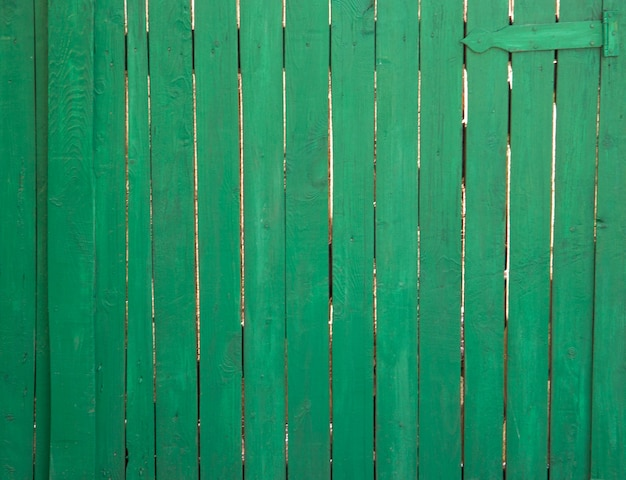 A wooden fence that is painted with green paint. there's a door loop on top. the desks are not so tight to each other.