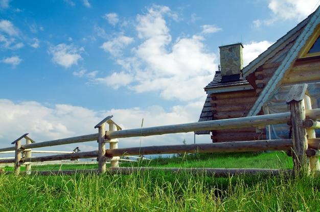 Rete fissa di legno con una casa dietro