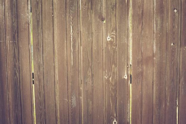 素朴な板茶色の樹皮の木の質感と木製のフェンス