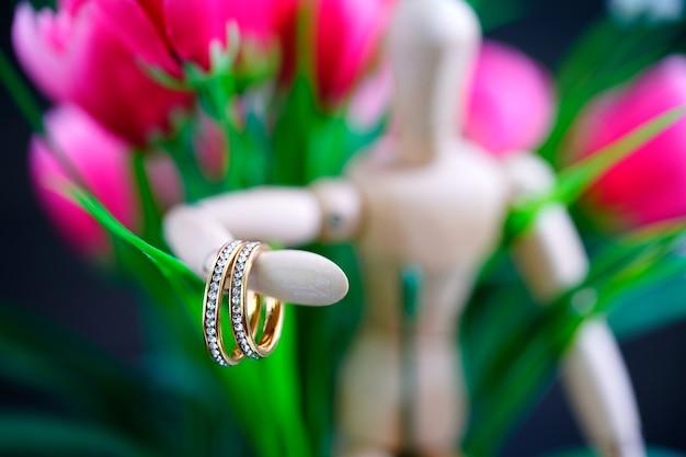 金色の結婚指輪を保持している木製の図