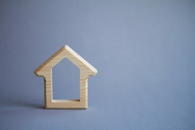 Wooden figure of house on gray, eco friendly to environment