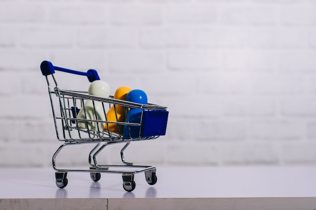 ショッピングのコンセプトを持つショッピングカートの木製フィギュア。
