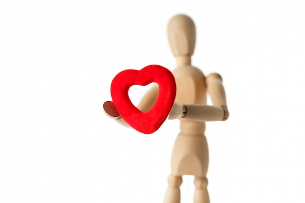 The wooden figure of a man holds in his hands a red heart on a white surface, gives the heart