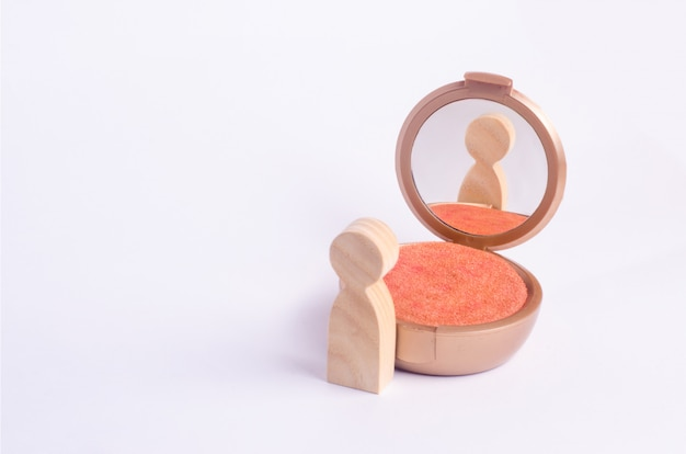 A wooden figure of a man looks in the mirror
