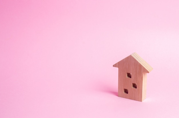 Wooden figure of a multi-storey house on a pink background. three-story house.