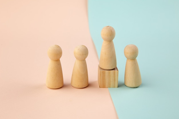 Wooden figure standing on the box for show influence and empowerment on colorful background. concept of business leadership for leader team.