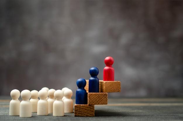 Деревянная фигура стоит на ящике для демонстрации влияния и расширения возможностей. концепция бизнес-лидерства для команды лидеров, успешного победителя конкурса и лидера с влиянием