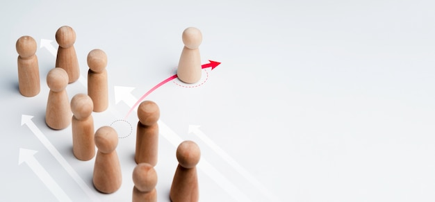 The wooden figure standing on red arrow, change direction and pointing in a different way from group on white background with copy space. leadership, unique, business for innovative solution concept.