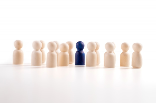Wooden figure standing with team to show influence and empowerment.