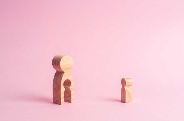 A wooden figure of a woman and a child stands near the magnifying glass.