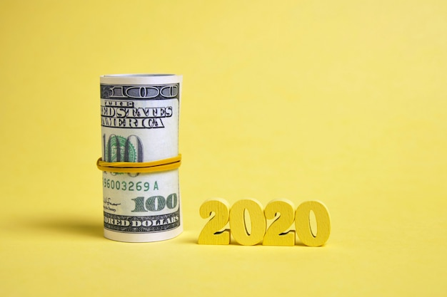 Wooden figures 2020  with a roll of dollars tied with an elastic band background