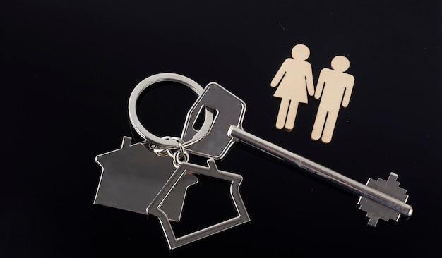 Деревянные фигуры и ключ на черном фоне. покупка концепции дома