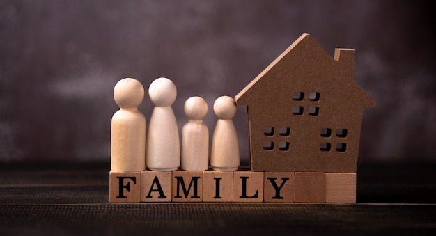 Wooden figures family standing beside a wooden house on a wooden cube that writes the word family.