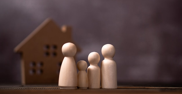 Wooden figures family standing in front of a wooden house. the concept of protection and safety