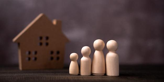 Деревянная фигура семьи стоя перед деревянным домом.