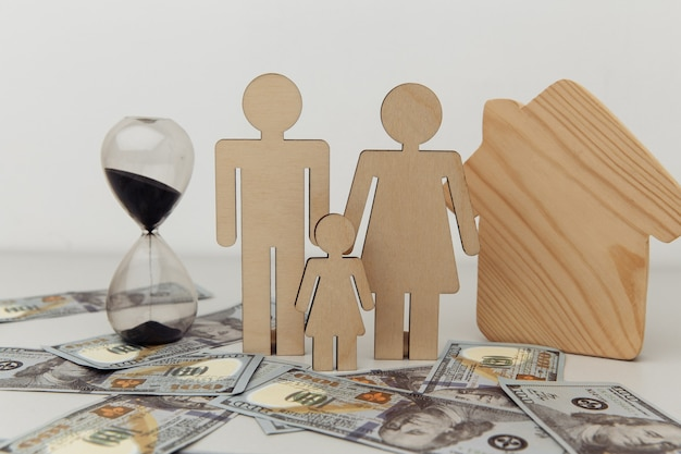 Wooden figures of family with house and hourglass savings and profit concept