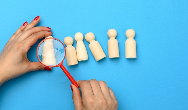 Wooden figures of men on a blue background and a red magnifying glass. recruitment concept, search for talented and capable employees, career growth