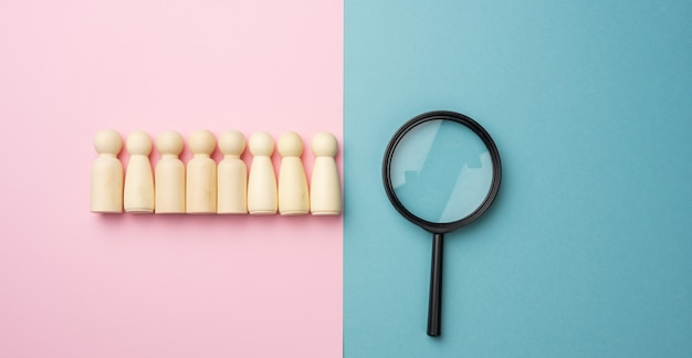 Wooden figures of men on a blue surface and a black magnifying glass. recruitment concept, search for talented and capable employees, career growth, flat lay