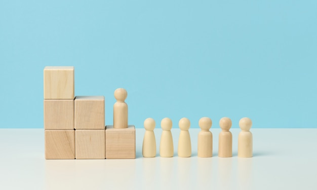 Wooden figures of men on a ladder made of blocks. the concept of career advancement, starting at work, achieving goals. blue background