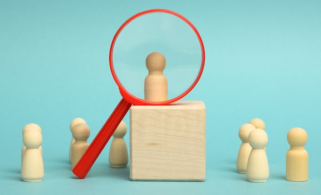 Wooden figures of men stand on a beige background and a plastic magnifying glass. recruitment concept, search for talented and capable employees, career growth