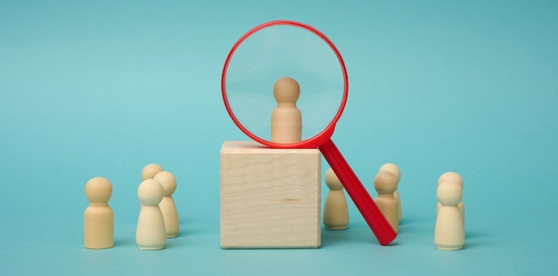 Wooden figures of men stand on a beige background and a red plastic magnifying glass. recruitment concept, search for talented and capable employees, career growth