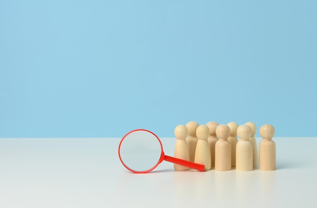 Wooden figures of men stand on a blue background and a redplastic magnifying glass.