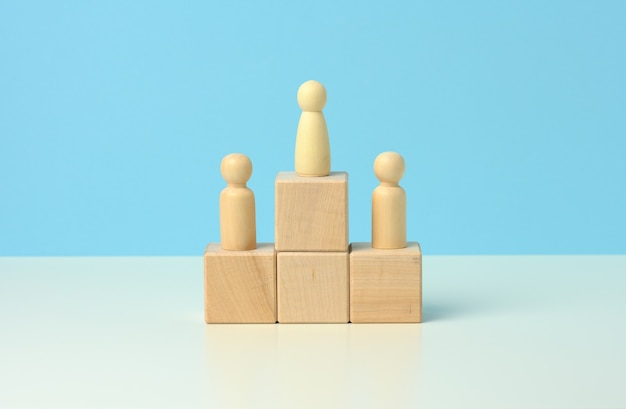 Wooden figures of men stand on a pedestal of their cubes on a blue background. the concept of rivalry in sports, business and life. achieving success and leadership,