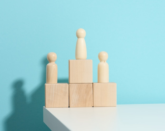 Wooden figures of men stand on a pedestal of their cubes on a blue background. the concept of rivalry in sports, business and life. achieving success and leadership
