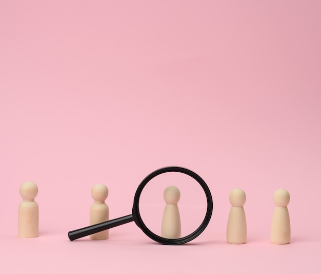 Wooden figures of men stand on a pink surface and a black magnifying glass