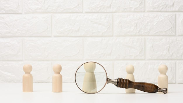 Wooden figures of men stand on a white background and a magnifying glass. recruitment concept, search for talented and capable employees, career growth Premium Photo