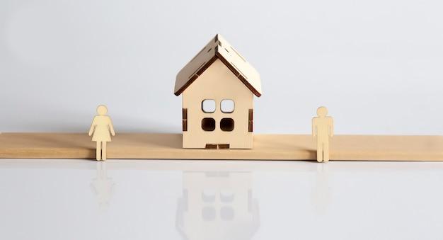 はかりの上の男性と女性の木製の人物とそれらの間の家